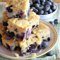 pieces of blueberry cornbread stacked on a plate with a bowl of blueberries in the background- set on a green towel on a wooden surface