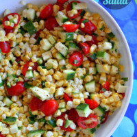 overhead shot of white bowl of fresh corn, tomato and zucchini salad set on a blue and green polka dot tablecloth