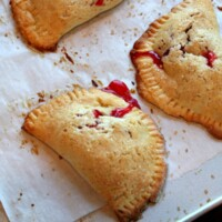three berry hand pies on a baking sheet lined with parchment paper