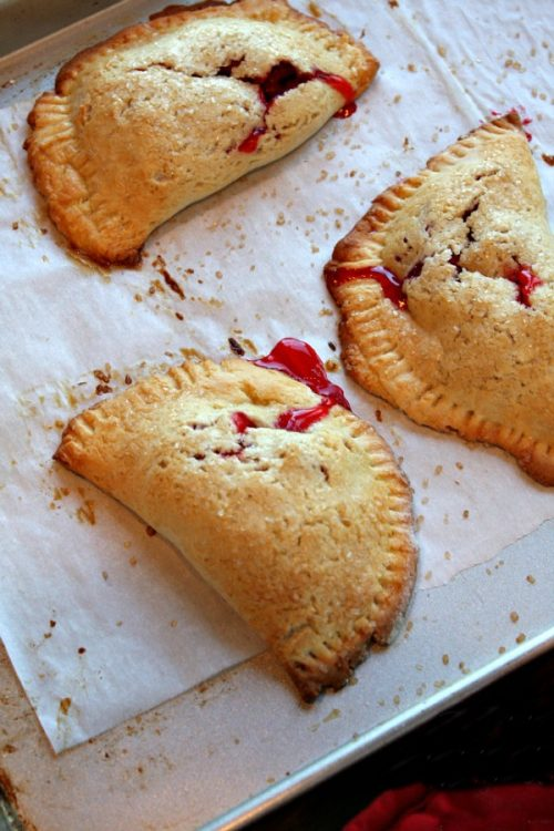 Three baked Berry Hand Pies on a baking sheet lined with parchment paper