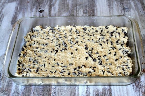 How to Make Oreo and Caramel Stuffed Chocolate Chip Cookie Bars with a layer of cookie dough spread into the bottom of pyrex pan