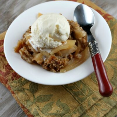 apple crisp topped with ice cream in a white bowl