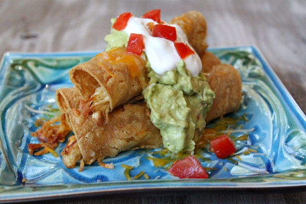 Easy Baked Chicken Taquitos garnished with sour cream and guacamole on a blue and green decorative plate