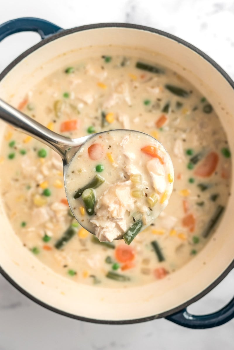 creamy chicken and rice soup in a pot with a ladle