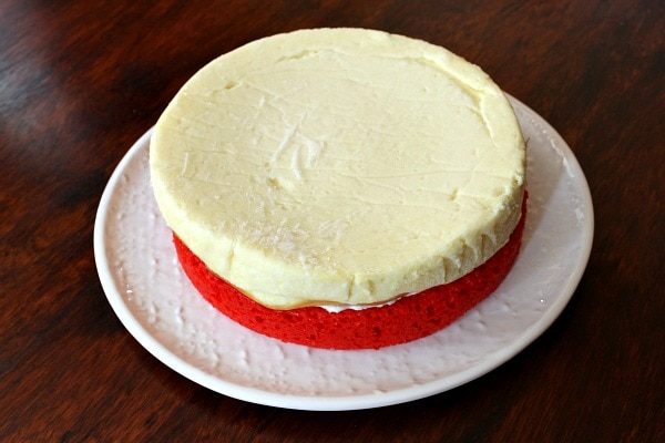 red layer of cake on a white plate topped with a cheesecake layer