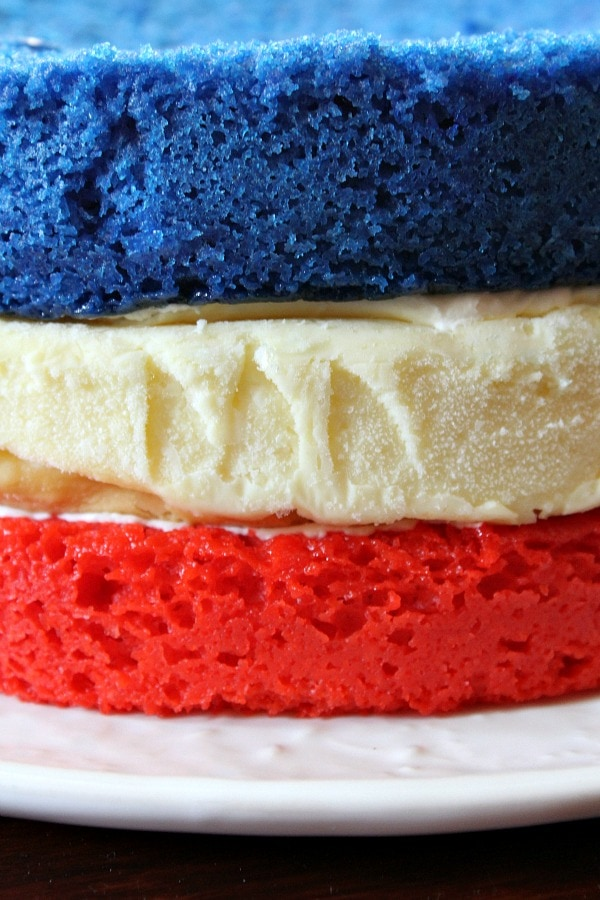 three layers of cake close up- red cake, white cheesecake and blue cake on top