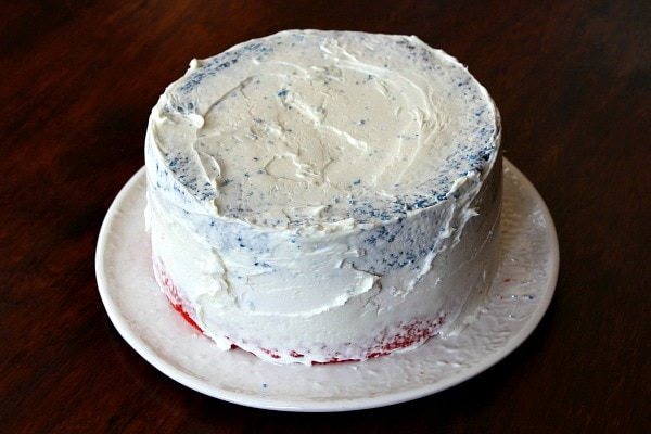white frosting on a red white and blue layer cake on a white plate