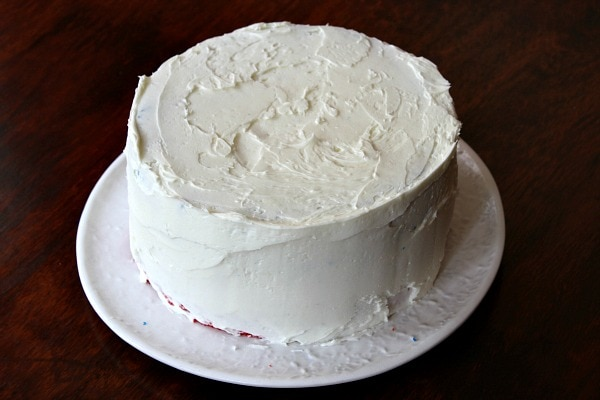 white frosted layer cake on a white plate