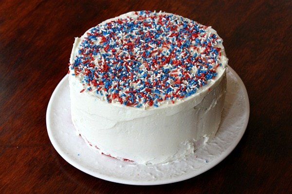 red white and blue sprinkles on top of a white layer cake on a white plate