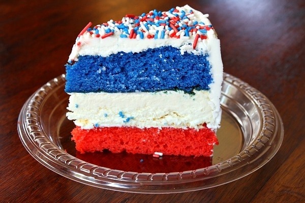 slice of red, white and blue cheesecake cake on a plastic plate on a wood surface