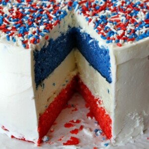 red, white and blue cheesecake cake sliced into to see the inside- displayed on a white plate