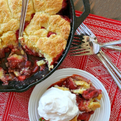 strawberry shortcake skillet cobbler in black skillet with serving of cobbler with cream on the side
