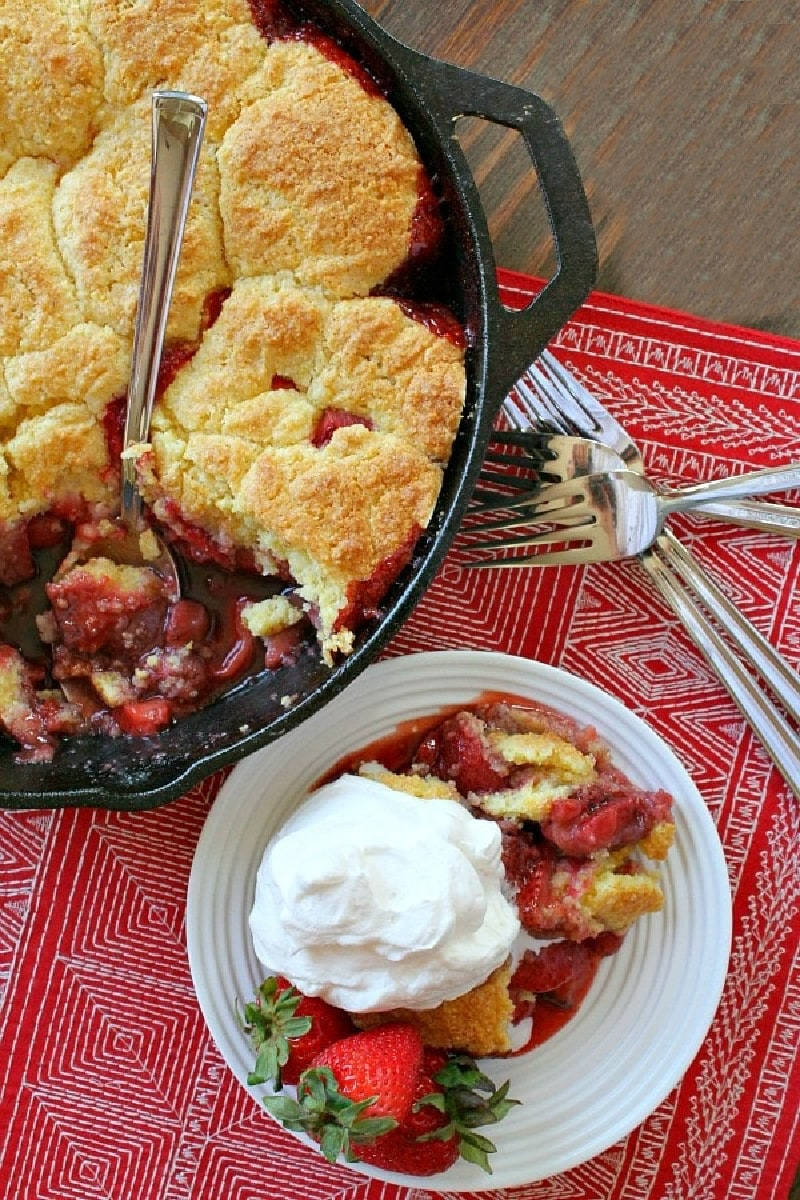 Strawberry shortbread cobbler in a black pan with serving of cobbler with cream on the side