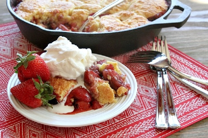 portion of strawberry shortbread cobbler on white plate with whipped cream