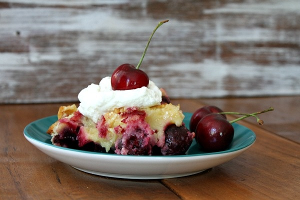 serving of Easy Cherry Cobbler on a green plate set on a wooden table. Garnished with whipped cream and fresh cherries with stems