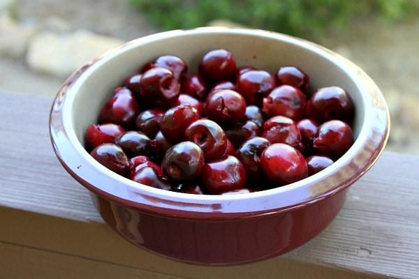 fresh cherries in a round burgundy casserole dish set on a wooden railing