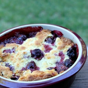 cherry cobbler in a round burgundy casserole dish sitting on a wooden railing with green background