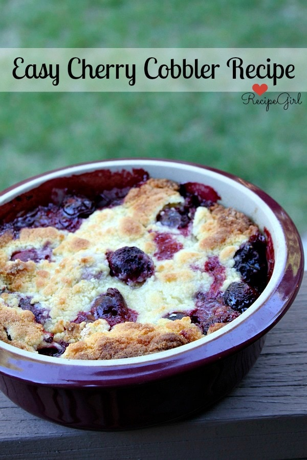 Cherry Cobbler in a round burgundy casserole dish on a wooden railing with green background