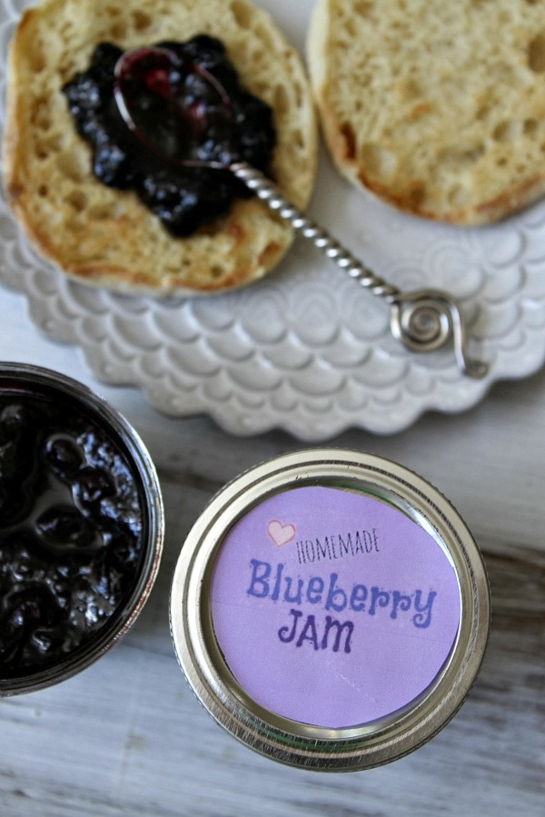 overhead shot of blueberry jam in a jar with the lid displayed too, The lid has a purple label. english muffin with spoon of jam on it on a plate.