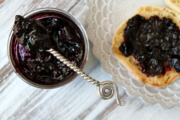overhead shot of Homemade Blueberry Refrigerator Jam in a jar with a spoonful of jam sitting on top. english muffin with jam on a plate alongside