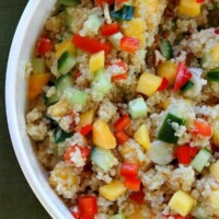overhead shot of half of a peach and pecan quinoa salad in a white bowl