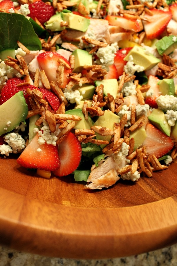 close up of strawberry chicken salad in a big wooden bowl