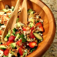strawberry chicken salad in a big wooden bowl with wooden serving spoons