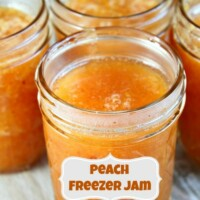 peach freezer jam with a label and several more jars of peach jam in the background.