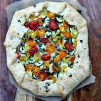 overhead shot of rustic tomato and zucchini tart on parchment paper sitting on a wooden cutting board