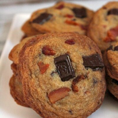 bacon bourbon chocolate chunk cookies displayed on a white plate