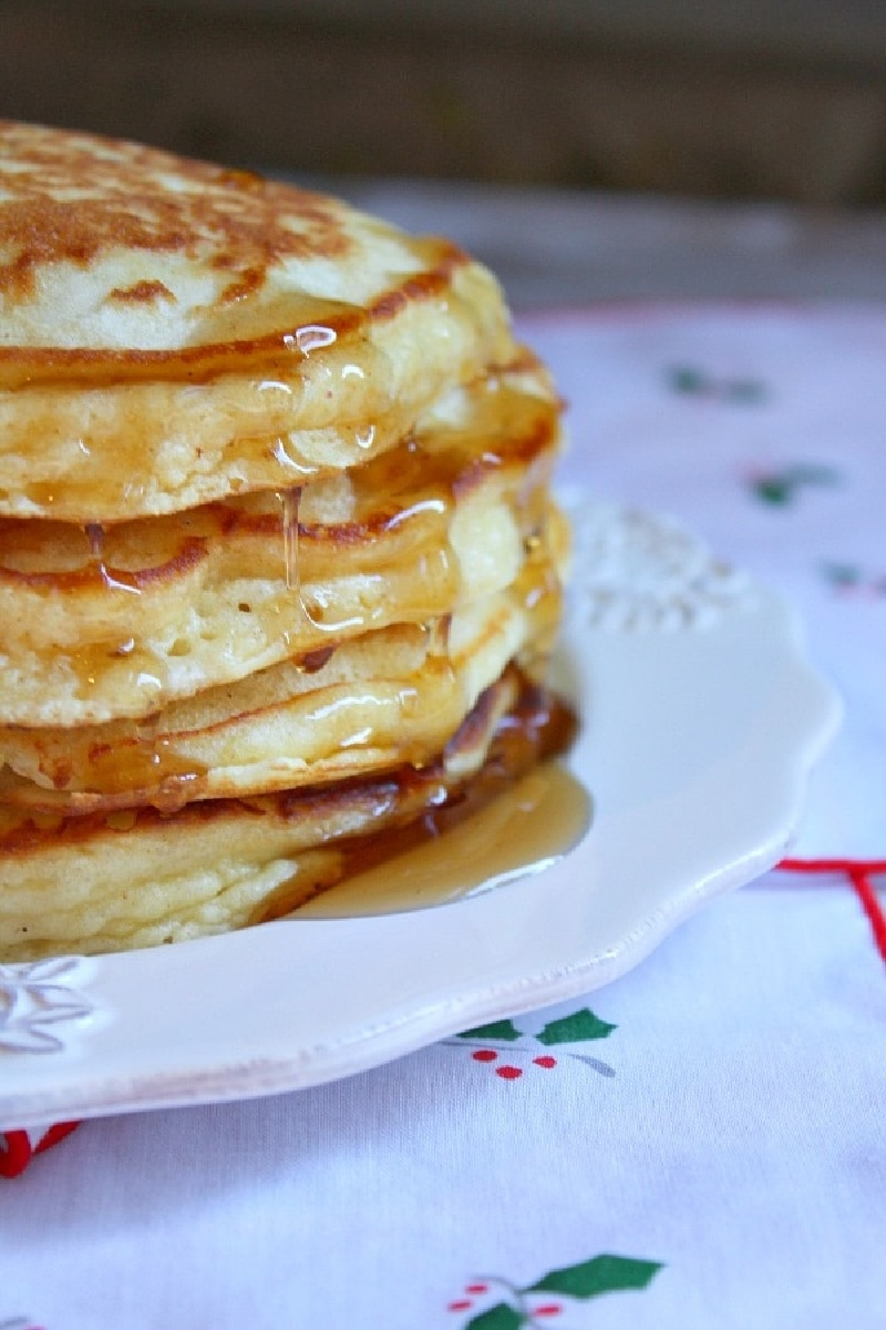 eggnog pancakes in a stack with syrup