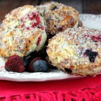 three berry scones on a white platter with fresh berries scattered. Pink cloth napkin underneath
