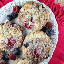 overhead shot of fresh berry scones on a white platter with scattered fresh berries around. pink cloth napkin underneath