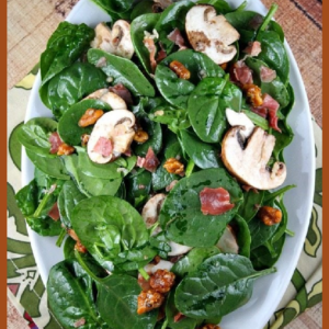 pinterest image for spinach salad on a white plate