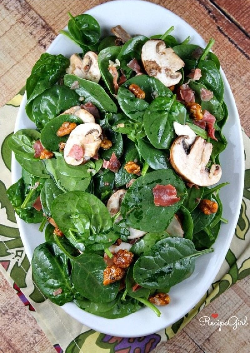 spinach salad on a white platter