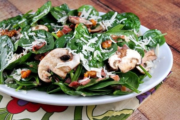 Spinach Salad with Hot Prosciutto Dressing on a white platter