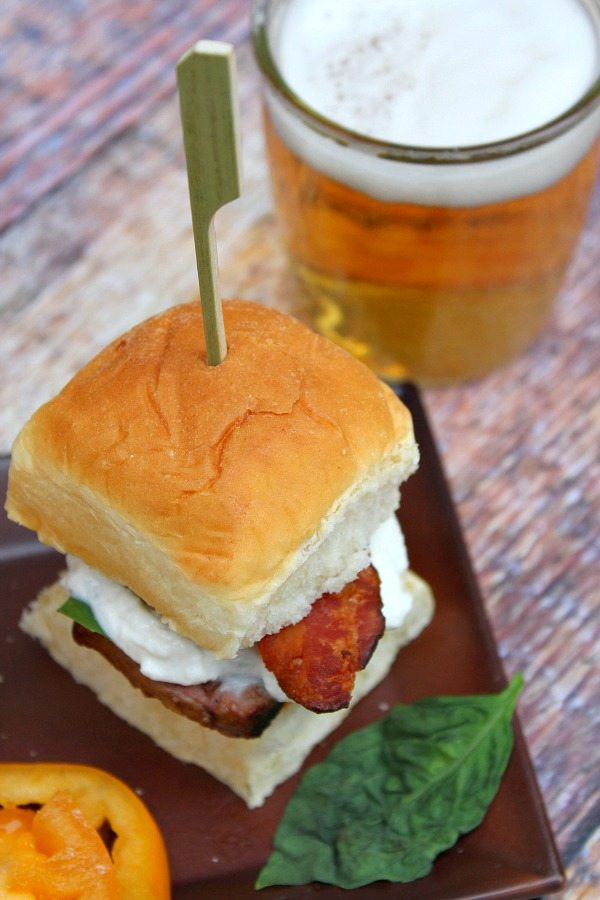 looking down on a filet mignon caprese slider with a glass of beer