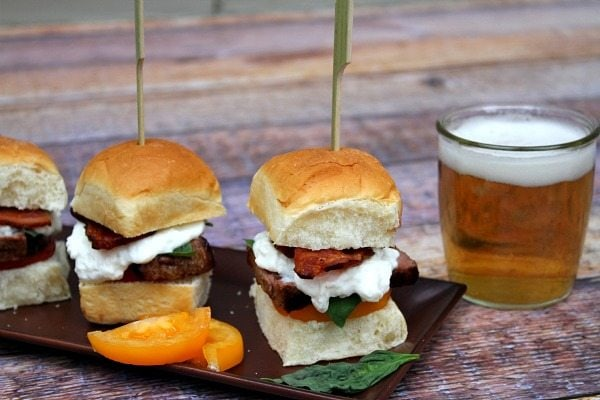 tray of filet mignon caprese sliders each skewered with a long sandwich pick. Beer on the side