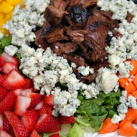 grilled steak summer salad on a white plate with steak piled in the middle surrounded by blue cheese and vegetables and fruit