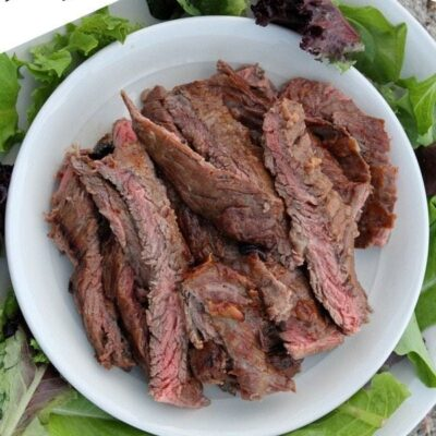 overhead shot of marinated grilled and sliced skirt steak on a white plate surrounded by lettuce leaves