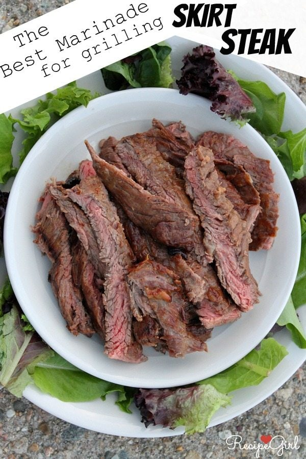 Grilled Skirt Steak sliced and displayed on a white platter surrounded by lettuce leaves