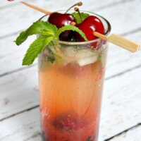 cherry mojito displayed on a white wood plank surface garnished with fresh cherries and mint