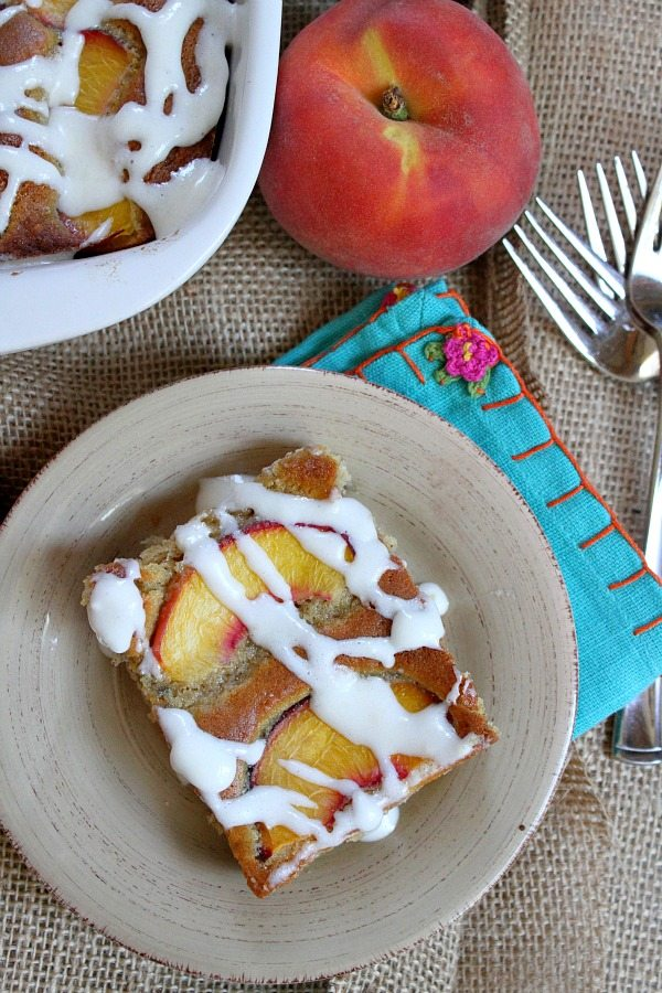 overhead shot of slice of fresh peach cake on a beige plate set on top of turquoise napkin with forks and a fresh peach in the background