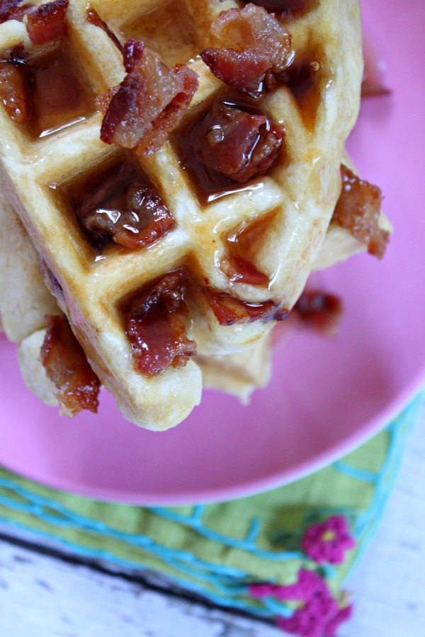 Looking down on a maple bacon waffle on a pink plate