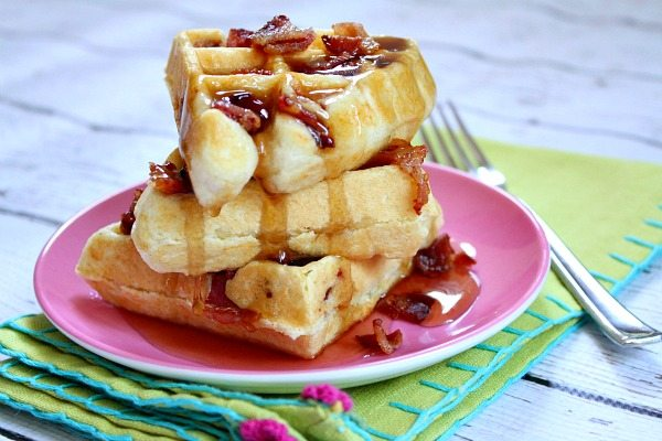 three waffles stacked with maple syrup and bacon