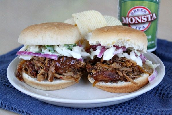Two Slow Cooker Pulled Pork sliders on a white plate with potato chips and a can of green monsta beer, set on a blue napkin