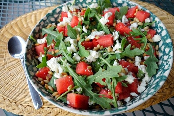 blue and white bowl filled with watermelon, feta and arugula salad