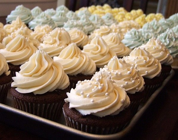 wedding cupcakes in assorted colors on a baking sheet