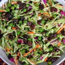 overhead shot of a bowl of broccoli slaw set on top of a burgundy striped cloth napkin