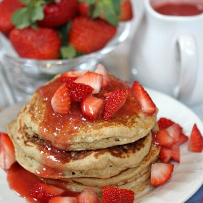 stack of strawberry ricotta pancakes. lots of fresh strawberries and strawberry sauce on top with fresh strawberries and pitcher of sauce in background.